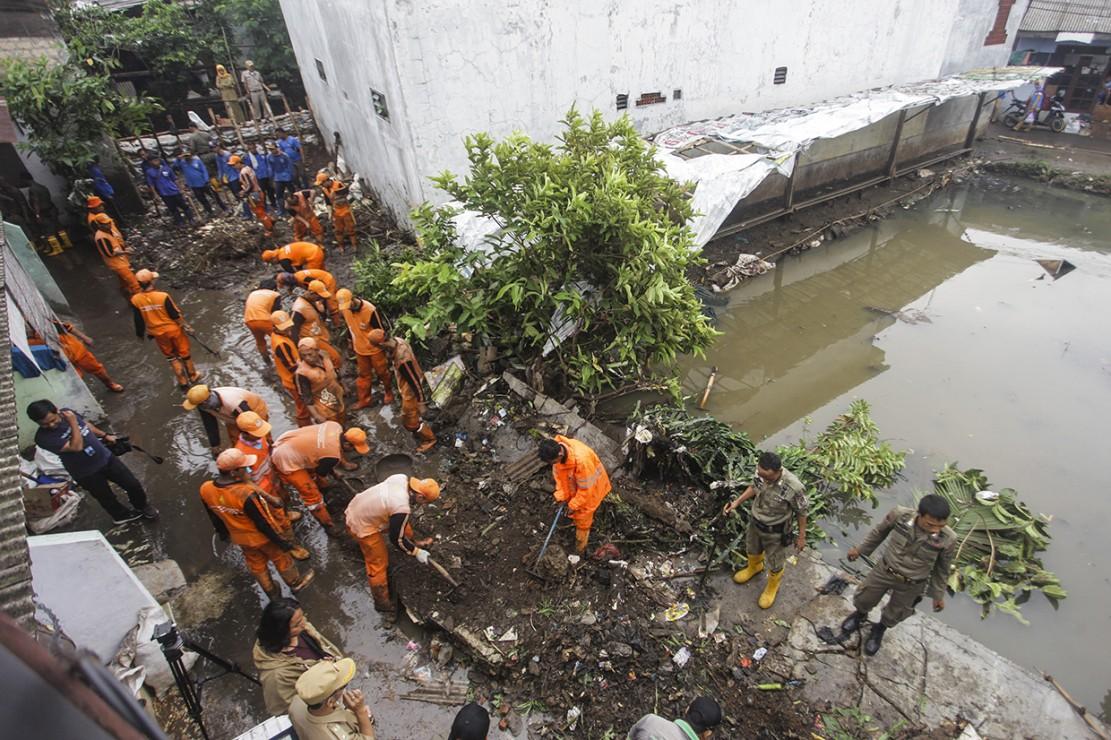 Petugas PPSU membersihkan lumpur yang menggenangi jalan pemukiman warga karena tanggul aliran Kali Pulo jebol di Kelurahan Jati Padang, Kecamatan Pasar Minggu, Jakarta.