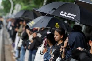 Puluhan peserta aksi kamisan melakukan aksi diam menggunakan payung hitam di depan Istana Negara, Jakarta. Aksi kamisan tersebut diselenggarakan memperingati 12 tahun berlangsungnya aksi kamisan yang rutin digelar setiap hari kamis di depan Istana Negara.