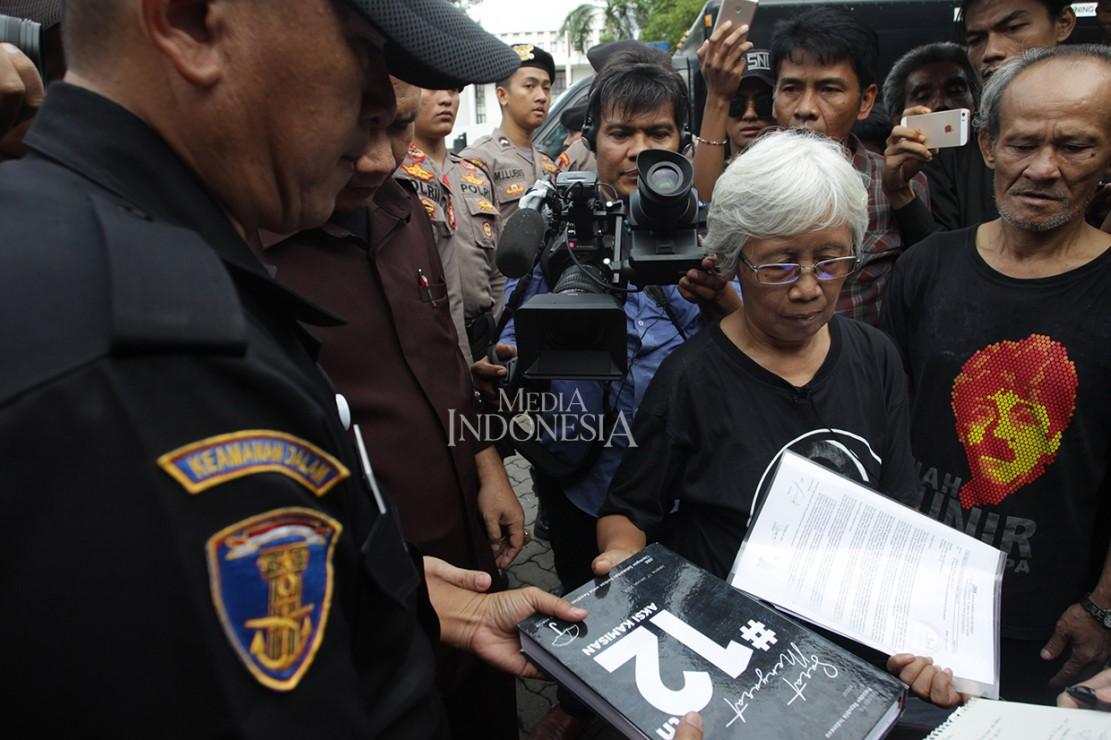 Meskipun sempat dihalang-halangi oleh petugas Kepolisian, Maria Catarina Sumarsih tetap mengantarkan catatan tersebut kepada pihak pengamanan dalam kantor Sekretariatan Negara.