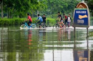 Sejumlah anak melintas di Jalan Raya yang terendam banjir di Porong, Sidoarjo, Jawa Timur.