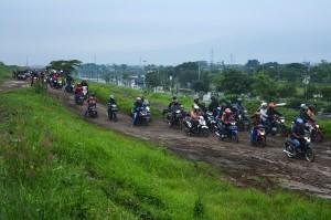 Sejumlah pengendara sepeda motor melewati tanggul penahan lumpur Lapindo untuk menghindari banjir di Porong, Sidoarjo, Jawa Timur.