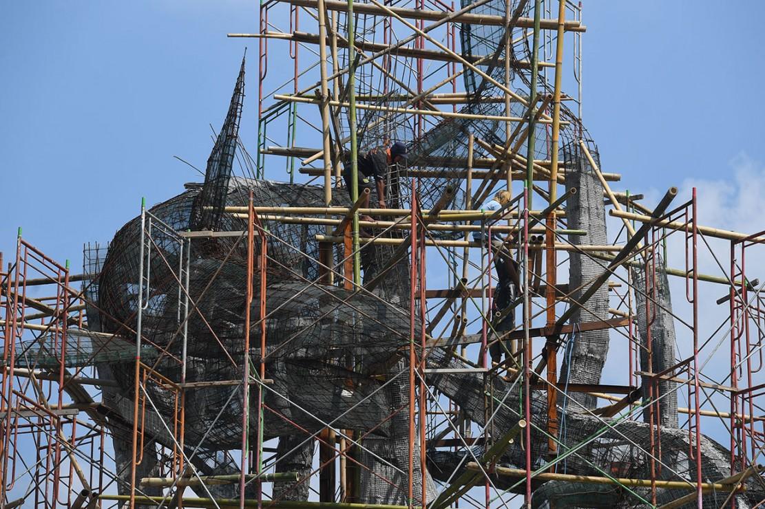 Pekerja tengah menyelesaikan pembangunan patung Suro dan Boyo di Taman Suroboyo, Kenjeran, Surabaya, Jawa Timur, Jumat, 18 Januari 2019.