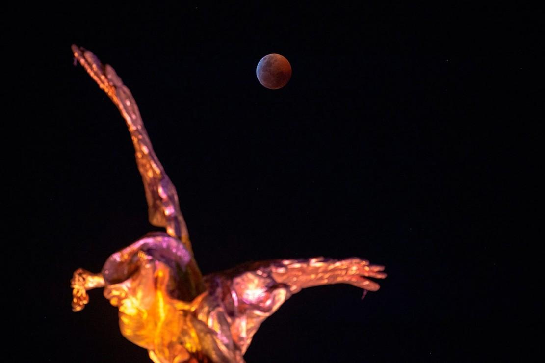 Penampakan super blood wolf moon di atas Angel de la Independencia, Mexico City. AFP Photo/Alfredo Estrella