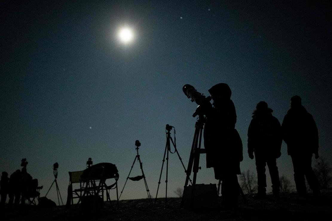 Warga melihat fenomena terjadinya super blood wolf moon dengan teleskop di Wina, Austria. AFP Photo/Georg Hochmuth