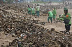 Sejumlah petugas membersihkan tumpukan sampah yang berserakan di kawasan Pantai Kuta, Badung, Bali.