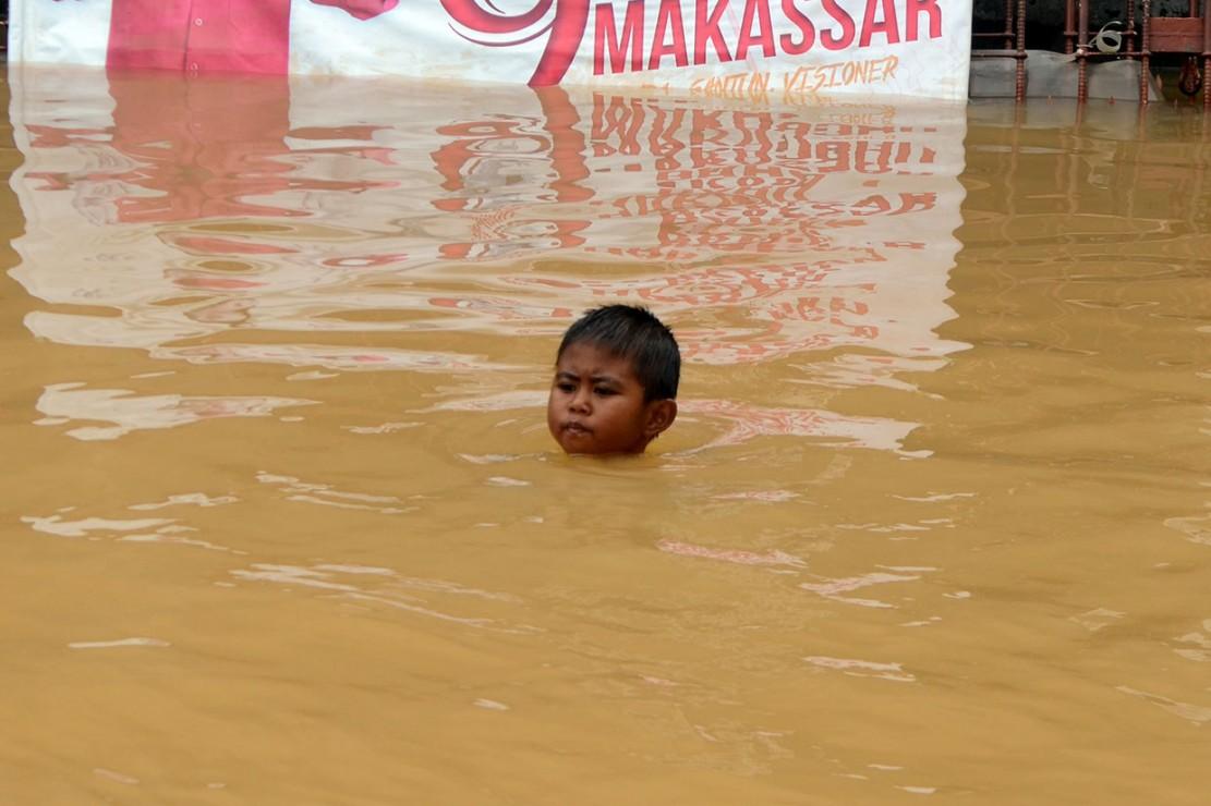 Seorang anak bermain di lokasi banjir di Perumahan Bumi Bung Permai, Makassar.