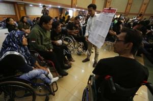 Petugas menunjukkan contoh surat suara saat sosialisasi pendidikan pemilih dan simulasi Pemilu bagi penyandang disabilitas di Aula Kementerian Sosial, Jakarta.