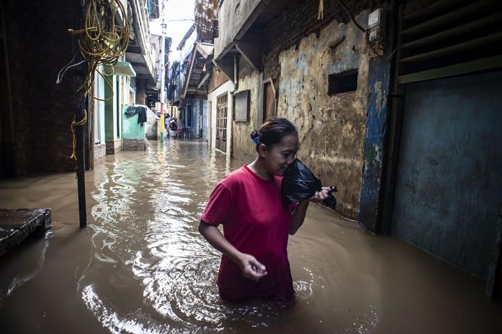 Warga Kebon Pala Cuci Baju dengan Air Banjir Luapan Ciliwung